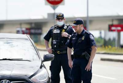 Customs and Border Protection officers direct a driver on who missed the last turn before entry into Canada on how to turn around at the Peace Arch border crossing into the U.S., Tuesday, June 8, 2021, in Blaine, Wash. The border has been closed to nonessential travel since March 2020. (AP Photo/Elaine Thompson)