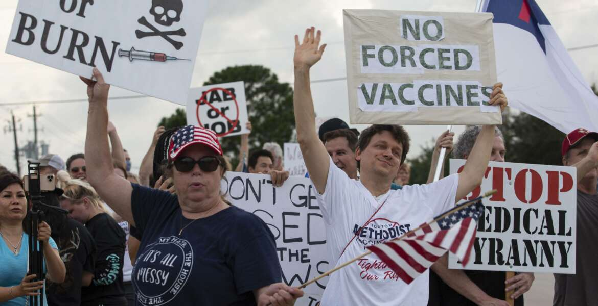FILE - In this June 7, 2021, file photo, demonstrators at Houston Methodist Baytown Hospital in Baytown, Texas, wave at cars that honk at them to support their protest against a policy that says hospital employees must get vaccinated against COVID-19 or lose their jobs. A  federal judge dismissed their lawsuit, saying if workers don't like the rule, they can go find another job. (Yi-Chin Lee/Houston Chronicle via AP)
