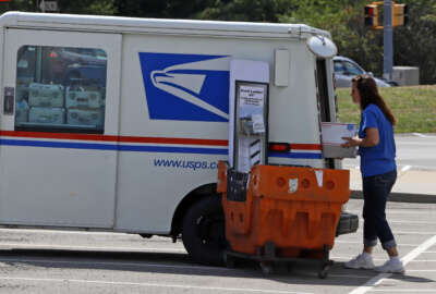 A postal worker loads a delivery vehicle at the United States Post Office in Cranberry Township, Pa., Wednesday, Aug. 19, 2020. (AP Photo/Gene J. Puskar)