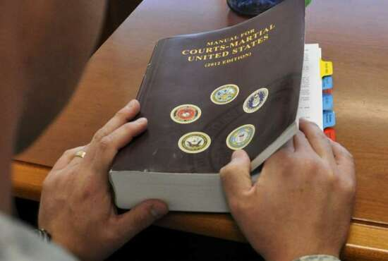 U.S. service member examines a Manual for Courts-Martial. (U.S. Air Force/Staff Sgt. Nicholas Rau)
