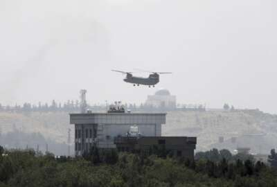 FILE - In this Sunday, Aug. 15, 2021 file photo, a U.S. Chinook helicopter flies near the U.S. Embassy in Kabul, Afghanistan, as diplomatic vehicles leave the compound amid the Taliban advance on the capital. (AP Photo/Rahmat Gul)