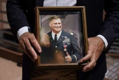 Retired Army Col. Arnold Strong holds a photograph as himself with his military uniform Thursday, Aug. 5, 2021, in Long Beach, Calif. President Joe Biden asked the Pentagon last week to look at adding the COVID-19 vaccine to the military's mandatory shots.