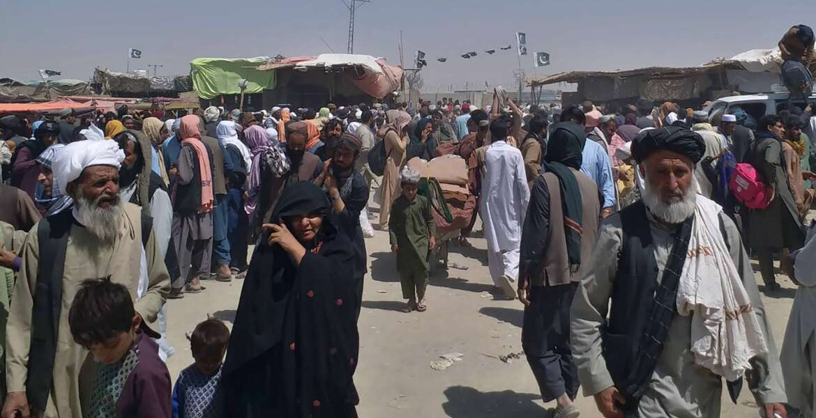 Afghan families wait for transport after entering Pakistan through a border crossing point in Chaman, Pakistan, Tuesday, Aug. 24, 2021. (AP Photo/Jafar Khan)