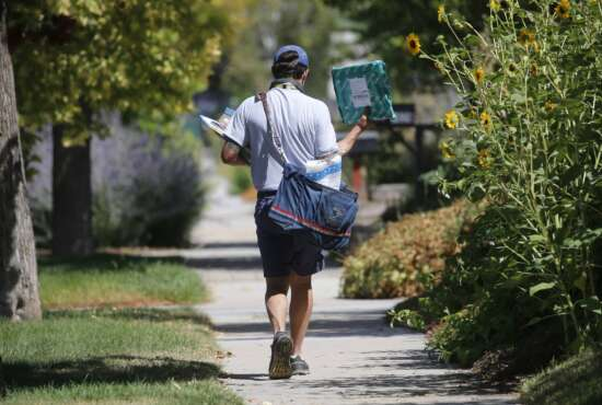 FILE - In this Aug. 17, 2020, file photo, a United States Postal Service carrier delivers mail to homes in Salt Lake City. A Center for Public Integrity investigation finds that the U.S. Postal Service regularly cheats mail carriers out of their pay. Arbitrators and federal investigators have found managers at hundreds of post offices around the country have illegally underpaid hourly workers for years. (AP Photo/Rick Bowmer, File)
