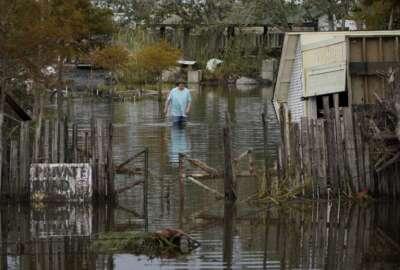 A man walks down a flooded street in the aftermath of Hurricane Ida, Wednesday, Sept. 1, 2021, in Lafitte, La. (AP Photo/John Locher)