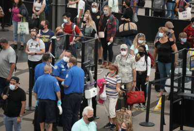 Travelers wear face coverings in the line for the south north security checkpoint in the main terminal of Denver International Airport Tuesday, Aug. 24, 2021, in Denver. Two months after the Sept. 11, 2001 attacks, President George W. Bush signed legislationcreating the Transportation Security Administration,a force of federal airport screeners that replaced the private companies that airlines were hiring to handle security. (AP Photo/David Zalubowski)