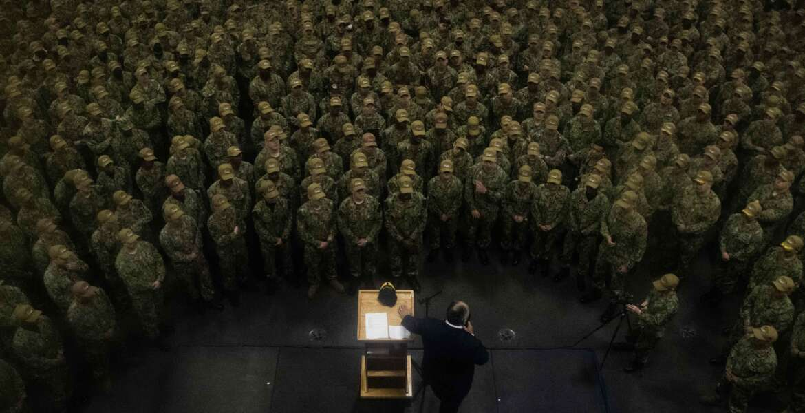 211026-N-DK722-1237 YOKOSUKA, Japan (Oct. 26, 2021) – Secretary of the Navy Carlos Del Toro speaks to the crew during an all hands call in the hangar bay of the U.S. Navy's only forward-deployed aircraft carrier USS Ronald Reagan (CVN 76). Ronald Reagan, the flagship of Carrier Strike Group 5, provides a combat-ready force that protects and defends the United States, and supports alliances, partnerships and collective maritime interests in the Indo-Pacific region. (U.S. Navy Photo by Mass Communication Specialist 2nd Class Cameron C. Edy)