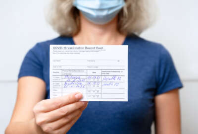 Moscow - Sep 12, 2021: Vaccinated young woman showing COVID-19 Vaccination Record Card, healthy person in mask after getting corona virus vaccine. Coronavirus vaccine shot and immunization mandate.