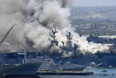 FILE - In this July 12, 2020, file photo, smoke rises from the USS Bonhomme Richard at Naval Base San Diego in San Diego, after an explosion and fire on board the ship at Naval Base San Diego. A Navy report has concluded there were sweeping failures by commanders, crew members and others that fueled the July 2020 arson fire that destroyed the USS Bonhomme Richard, calling the massive five-day blaze in San Diego preventable and unacceptable. While one sailor has been charged with setting the fire, the more than 400-page report, obtained by The Associated Press, lists three dozen officers and sailors whose failings either directly led to the ship's loss or contributed to it. (AP Photo/Denis Poroy, File)