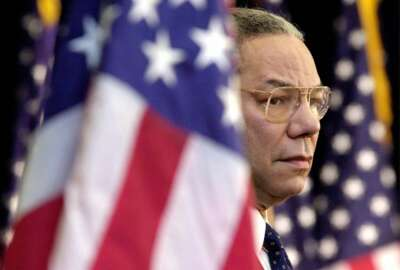FILE  - In this Feb. 15, 2001 file photo, Secretary of State Colin Powell looks on as President Bush addresses State Department employees at the State Department in Washington. Powell, former Joint Chiefs chairman and secretary of state, has died from COVID-19 complications, his family said Monday, Oct. 18, 2021. (AP Photo/Kenneth Lambert)