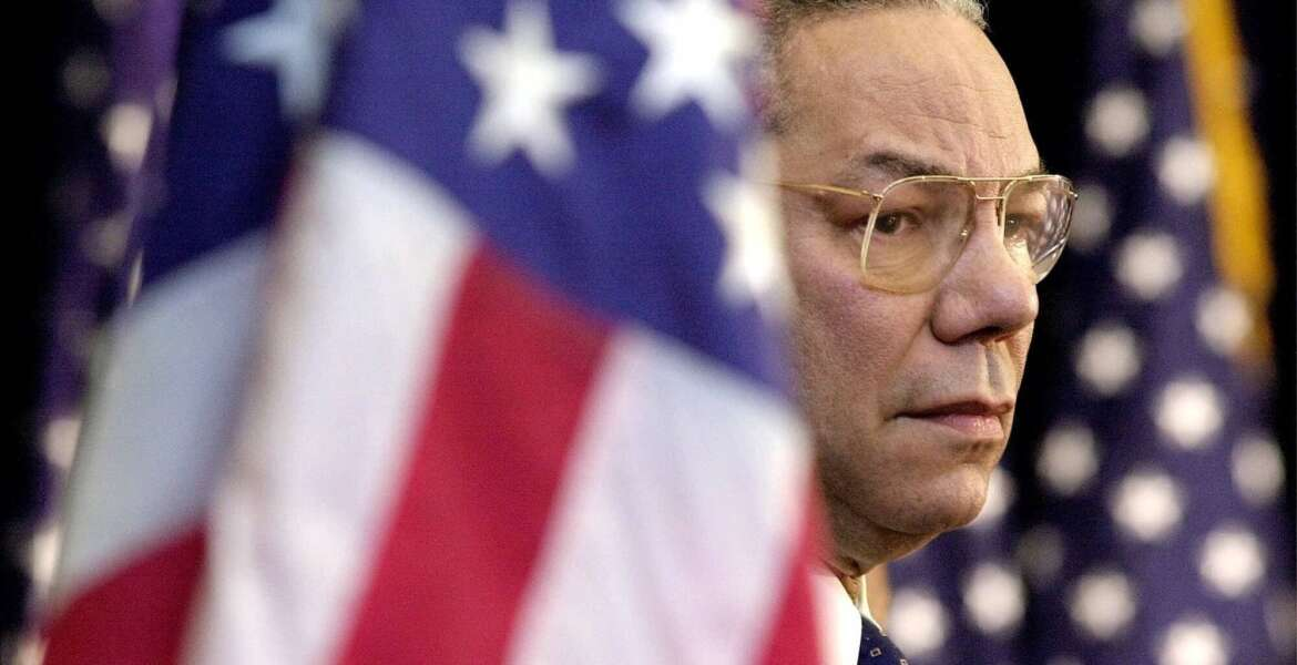 FILE  - In this Feb. 15, 2001 file photo, Secretary of State Colin Powell looks on as President Bush addresses State Department employees at the State Department in Washington. Powell, former Joint Chiefs chairman and secretary of state, has died from COVID-19 complications. In an announcement on social media Monday, the family said Powell had been fully vaccinated. He was 84. (AP Photo/Kenneth Lambert)