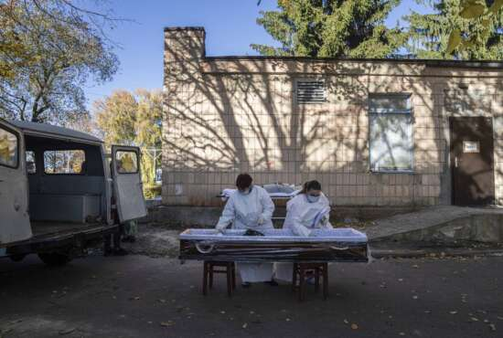FILE - In this Friday, Oct. 22, 2021 file photo, medical staff prepare a coffin for a body of a patient who died of coronavirus at the morgue of the city hospital 1 in Rivne, 300 kilometers (190 miles) west of Kyiv, Ukraine. Ukraine is suffering through a surge in coronavirus infections, along with other parts of Eastern Europe and Russia. While vaccines are plentiful, there is a widespread reluctance to get them in many countries —  though notable exceptions include the Baltic nations, Poland, the Czech Republic, Slovenia and Hungary. (AP Photo/Evgeniy Maloletka, File)