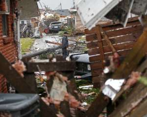 A man walks down the street past destroyed homes after a tornado tore through the  eastern part of New Orleans, Tuesday, Feb. 7, 2017.   The National Weather Service says at least three confirmed tornadoes have touched down, including one inside the New Orleans city limits. Buildings have been damaged and power lines are down. (AP Photo/Gerald Herbert)